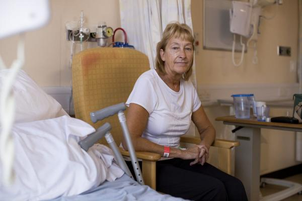 A blonde haired woman sits in a chair next to a hospital bed and a pair of crutches.