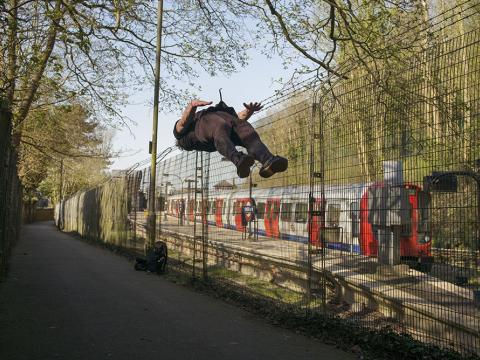 A man doing a backflip next to a tube line