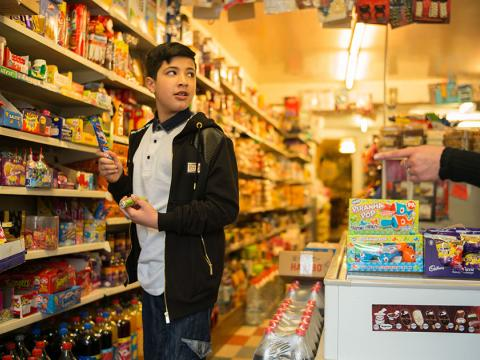 A boy in a sweet shop holding a chocolate bar